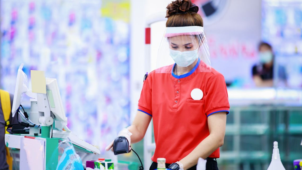 essential worker in retail customer service wearing PPE