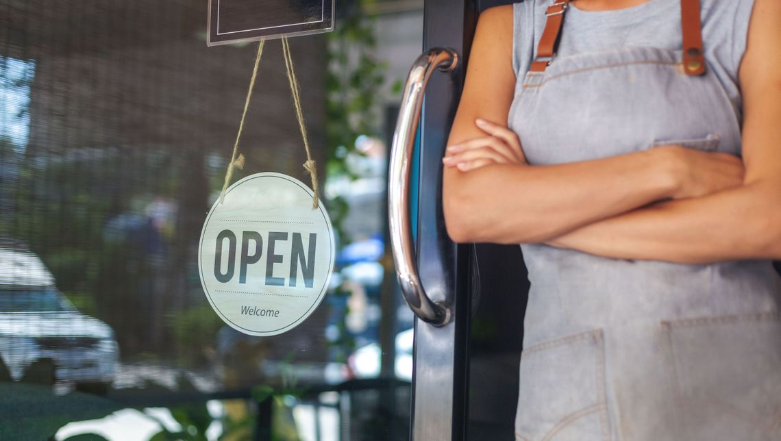 small business owner wearing apron leaning against storefront open sign in Ottawa